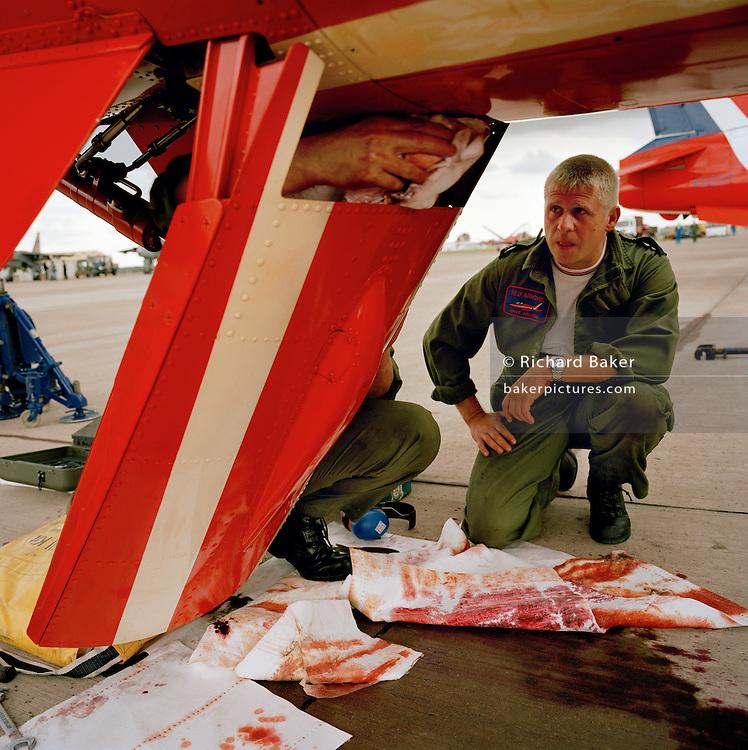Engineering ground staff of the Red Arrows, Britain's RAF aerobatic team, make repairs between training flights.