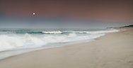 The full moon rises over surf kicked up as tropical storm Bertha passes by well off shore.