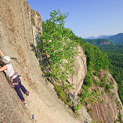 "A woman leads a climb of ""Top of the Prow"" on Cathedral Ledge.  Echo Lake State Park in North Conway, New Hampshire.  White Mountains."
