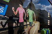 Detail of an illustration of two joggers wearing Karrimor sportswear, running in the window of Lillywhites, a retailer on Piccadilly Circus in central London. A man and woman run across the width of the window with a reflection of city architecture in the background while their shadows repeat sprinting arms and legs. Karrimor was founded and based in Lancashire, England, following World War II but as of 2013, the Karrimor brand remains and is licensed and used for marketing and product branding purposes. Sports Direct continue to sell Karrimor branded products, which are as of 2013 largely made in China rather than the UK.