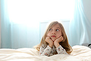 Young girl of seven daydreams in her bedroom