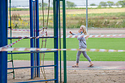 Schooling under COVID-19 young female Pupil with protective mask in the deserted playground at a Primary school. The outbreak of COVID-19 has forced governments around the world to impose a civil quarantine. The outcome of this is limited contact between people including students and teachers and minimal social interaction. Photographed at Kedem Primary School, Israel
