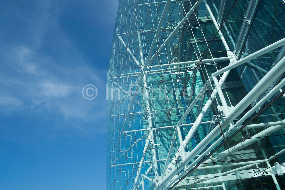 Glass structure of a building utilising modern architecture reflecting the sky in London, England, United Kingdom. The large transparent facade allows light to fill the interior.
