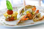 Prise de vue culinaire de 2 brochettes de crevettes accompagnées d'une petite salade sur une assiète posée sur une table du restaurant l'Hyppocampe de l'hôtel Le Méridien Nouméa situé en Nouvelle Calédonie.