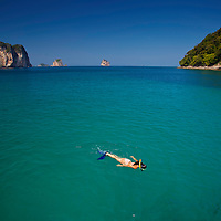 Woman snorkeling in turquoise waters near Chicken Island (Koh Gai), Krabi Thailand