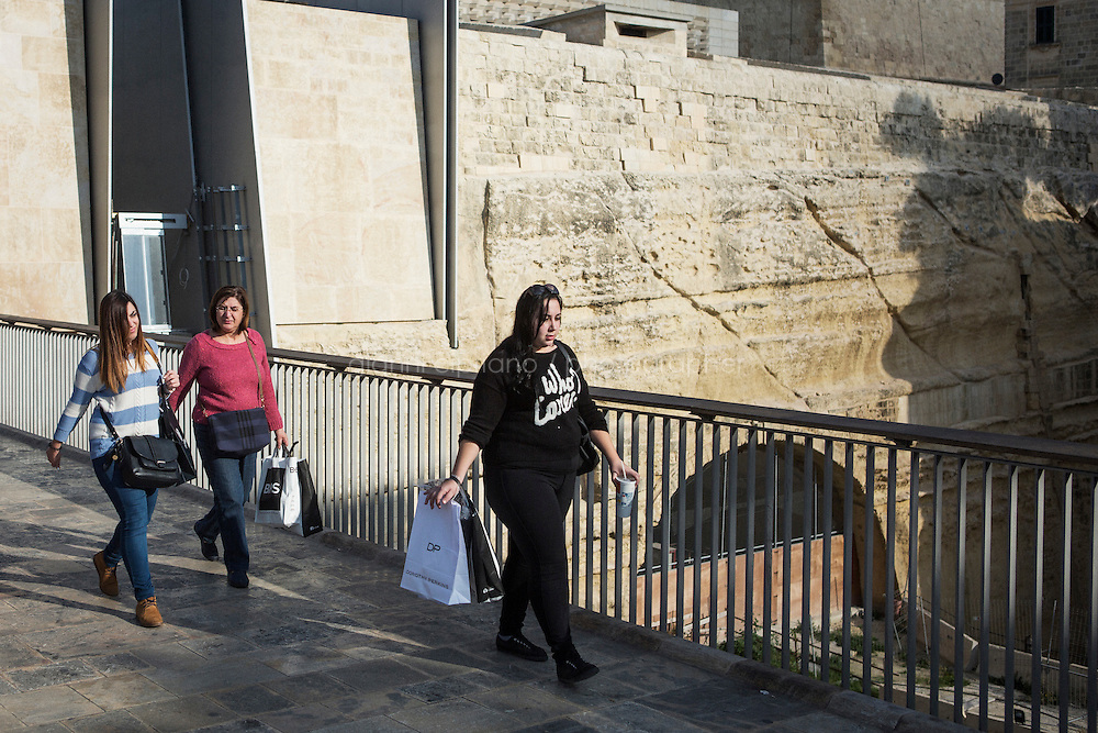 VALLETTA, MALTA - 7 DECEMBER 2015: An overweight woman walks by the City Gate of Valletta, Malta, on December 7th 2015. Malta hasthe highest overweight and obesity rates in the European Union, according to a report from the World Health Organisation.