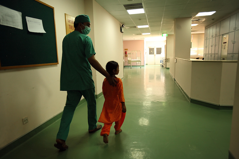 A doctor escorts a young patient down the hall inside the Children's Hospital at the Pakistan Institute of Medical Sciences, P.I.M.S., in Islamabad, Pakistan on Sept. 18, 2007.