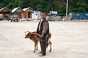 Young boy with his calf on the streets of Zhongdian, also known as Shangrila, Yunnan; China.