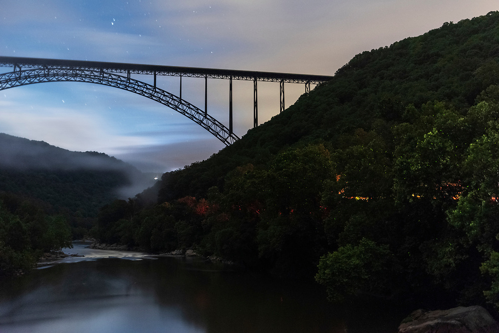 Thousands of lightning bugs light up the New River Gorge as the New River Gorge bridge towers above. As seen from the Fayette Station Road bridge in Fayettevile, W.V., on June 19, 2019. (Craig Hudson/The Charleston Gazette-Mail via AP)