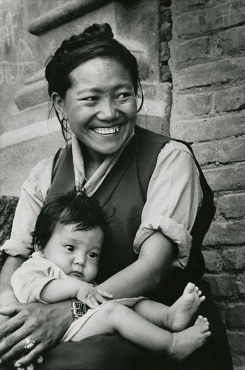 A woman and child in Kimtole village near the Buddhist shrine of Swyambhunath in Nepal's Kathmandu Valley. The woman wears Tibetan style clothing.
