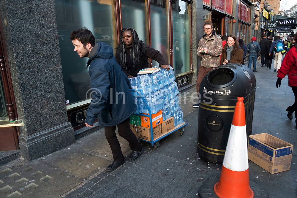 Street scene in Leicester Square of shop workers moving a pallet truck of water in London, England, United Kingdom. This remains one of London's tourism hot spots with entertainers and shop and space to hang out.  (photo by Mike Kemp/In Pictures via Getty Images)