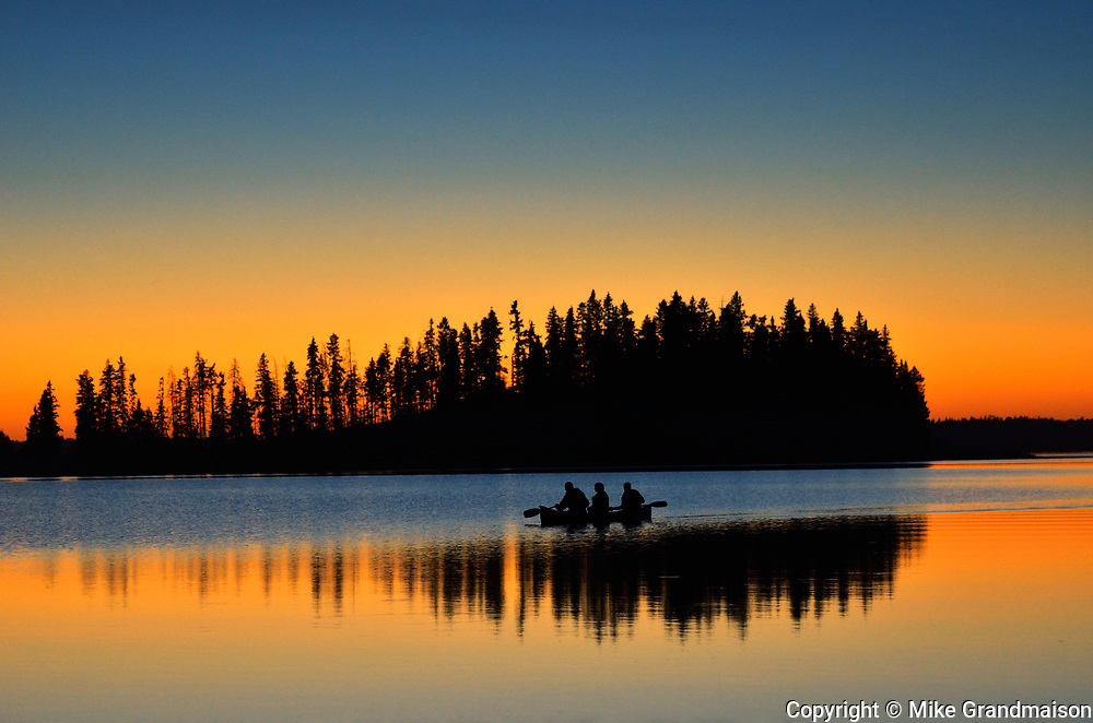 Family canoeing on Astotin Lake at sunset<br />Elk Island National Park<br />Alberta<br />Canada