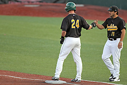 17 August 2013:  Tyler Shover and assistant coach Vinny Ganz bump fists as Shover reaches first base during a Frontier League Baseball game between the Rockford Aviators and the Normal CornBelters at Corn Crib Stadium on the campus of Heartland Community College in Normal Illinois