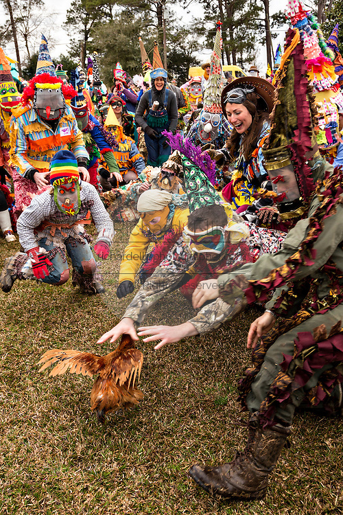 Costumed revelers race to catch a live chicken during the Faquetigue Courir de Mardi Gras chicken run on Fat Tuesday February 17, 2015 in Eunice, Louisiana. The traditional Cajun Mardi Gras involves costumed revelers competing to catch a live chicken as they move from house to house throughout the rural community.
