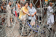 """May 12 - BANGKOK, THAILAND: People wait at a bus stop ringed with razor wire on Silom Road near the front line of the army and Red Shirt protesters Wednesday morning. The Thai government said Wednesday that time has run out for """"Red Shirt"""" protesters in Ratchaprasong and Sala Daeng Intersections in Bangkok and that a crackdown could come at any time. As news of the anticipated crackdown spread, Red Shirt protesters continued with an almost festive mood at their main stage but many of the sleeping areas around the protest site appeared to be empty. No official estimates on crowd size are available.  Photo by Jack Kurtz"""