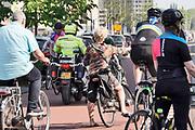 Nederland, Nijmegen, 27-4-2020 Een politieman op de motor heeft zojuist een groepje fietsers, wielrenners, aangesproken en een waarschuwing gegeven omdat ze te dicht op elkaar reden en zich niet aan de coronarichtlijnen hielden .Foto: Flip Franssen