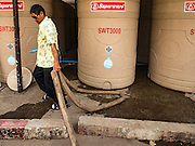 16 MARCH 2016 - PRACHIN BURI, PRACHIN BURI, THAILAND: A worker at Abhaibhubet Hospital in Prachin Buri, drags a water hose to tanks he was refilling from a water truck. The drought in Thailand is worsening and has spread to 14 provinces in the agricultural heartland of Thailand. Communities along the Bang Pakong River, which flows into the Gulf of Siam, have been especially hard hit since salt water has intruded into domestic water supplies as far upstream as Prachin Buri, about 100 miles from the mouth of the river at the Gulf of Siam. Water is being trucked to hospitals in the area because they can't use the salty water.        PHOTO BY JACK KURTZ
