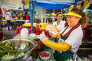 17 OCTOBER 2012 - BANGKOK, THAILAND:   A som tam (papaya salad) vendor packages a bag of vegan papaya salad during the Vegetarian Festival in Bangkok. Papaya salad is normally made with fish sauce, but some vendors hold the fish sauce out during the Vegetarian Festival. The Vegetarian Festival is celebrated throughout Thailand. It is the Thai version of the The Nine Emperor Gods Festival, a nine-day Taoist celebration celebrated in the 9th lunar month of the Chinese calendar. For nine days, those who are participating in the festival dress all in white and abstain from eating meat, poultry, seafood, and dairy products. Vendors and proprietors of restaurants indicate that vegetarian food is for sale at their establishments by putting a yellow flag out with Thai characters for meatless written on it in red.    PHOTO BY JACK KURTZ