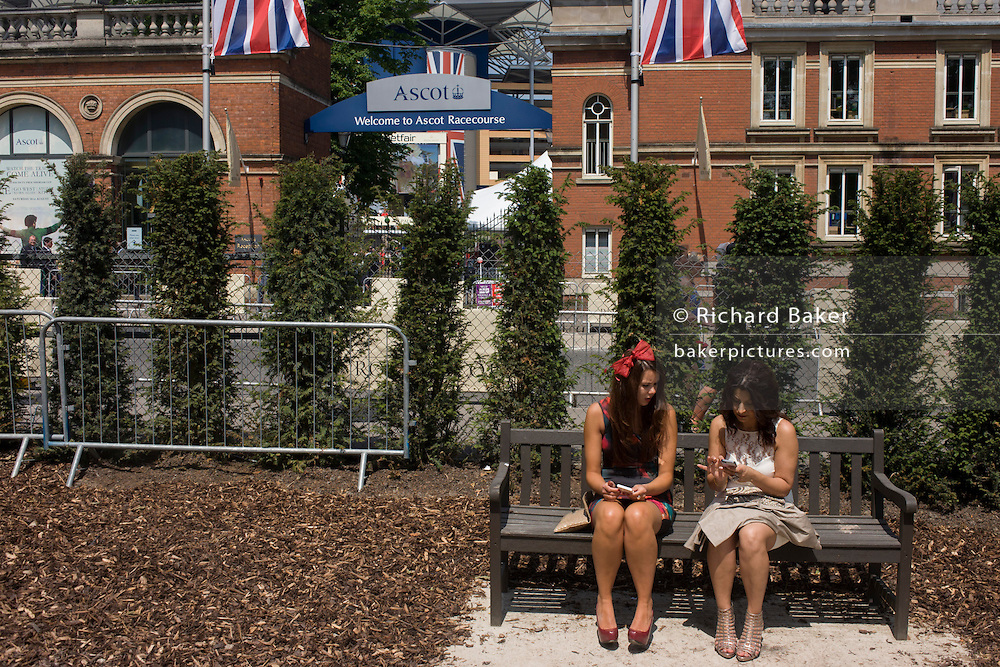 Teenage girls waiting in a transport movement area during the annual Royal Ascot horseracing festival in Berkshire, England. Royal Ascot is one of Europe's most famous race meetings, and dates back to 1711. Queen Elizabeth and various members of the British Royal Family attend. Held every June, it's one of the main dates on the English sporting calendar and summer social season. Over 300,000 people make the annual visit to Berkshire during Royal Ascot week, making this Europe's best-attended race meeting with over £3m prize money to be won.