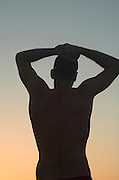 A lone silhouette of a male figure watching the sun set
