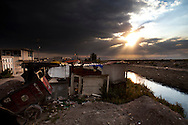 A shack on the edge of an open sewege canal on dry shores of Lake Texcoco.