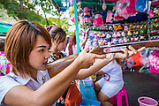 """27 NOVEMBER 2012 - BANGKOK, THAILAND: A Thai school girl takes aim with a pellet rifle at a shooting booth at the Wat Saket Temple Fair in Bangkok. Thailand is facing a rising tide of gun violence and is wrestling with how to curb it. Despite strict gun control laws, more and more guns are showing up in the country. Wat Saket, popularly known as the Golden Mount or """"Phu Khao Thong,"""" is one of the most popular and oldest Buddhist temples in Bangkok. It dates to the Ayutthaya period (roughly 1350-1767 AD) and was renovated extensively when the Siamese fled Ayutthaya and established their new capitol in Bangkok. The temple holds an annual fair in November, the week of the full moon. It's one of the most popular temple fairs in Bangkok. The fair draws people from across Bangkok and spills out in the streets around the temple.    PHOTO BY JACK KURTZ"""