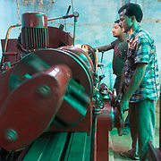CAPTION: Operating the lathe, powered by energy derived from biomass by DESI Power. LOCATION: Gayari, Araria District, Bihar, India. INDIVIDUAL(S) PHOTOGRAPHED: Mujaheed (in front) and Sohrab Alam (behind).