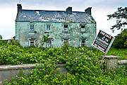 Derelict period house  with for sale estate agent auctioneer board in Moyasta, County Clare, West of Ireland
