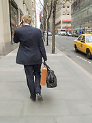 Business man walking and talking on his cell phone in the streets of New York City.