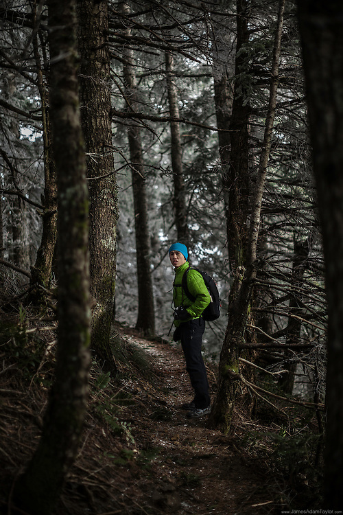 Near the summit of Table Mountain on the Washington side of the Columbia River Gorge, hiker Ray Phung stops along the trail to take in the unique forest.  At this elevation winds whip the clouds through the tree tops, leaving a layer of hoar frost. This crunchy crystalline coating sticks to the wind swept side of exposed needles and limbs, occasionally the high winds break small chunks free resulting in what appears to be a very light snowfall. <br /> The winter of 2013 and so far into 2014 has been an exceptionally dry year in the Cascades, perfect  for those looking to enjoy a steep hike along an exposed ridge line, but the tiny amount of water that freezes to surfaces directly from the clouds is hardly enough to keep the region moist during the traditionally dry summers. Only time will tell if precipitation in the cascades will increase in the coming months. If not the region may be in store for another harsh fire season.