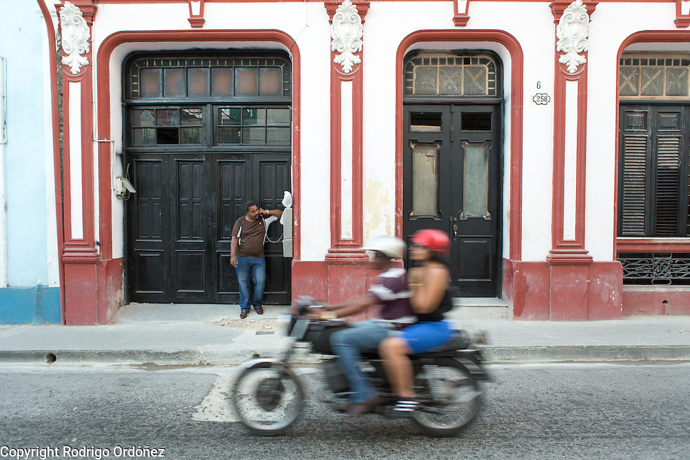 A man makes a phone call on a public payphone as motorists drive by in downtown Santiago de Cuba, Cuba, on December 26, 2014.