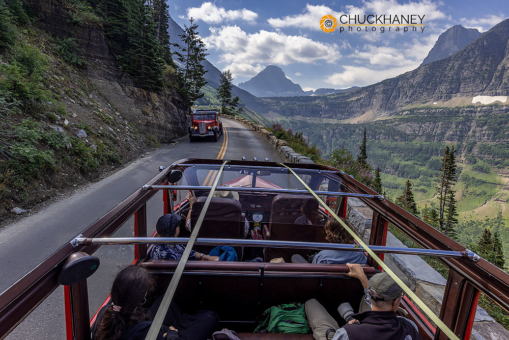 Iconic Red Jammer bus in motion in Glacier National Park, Montana, USA