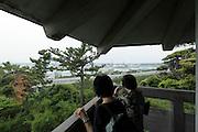 people looking out towards coastal heavy industry landscape