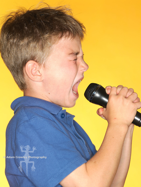 7 year old boy sings into a microphone.