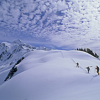 Skiers hike along Shukson Arm for out of bounds powder skiing near Washington's Mount Baker Ski Area.  Mount Shuksan and the Mount Baker Wilderness rise in the background.