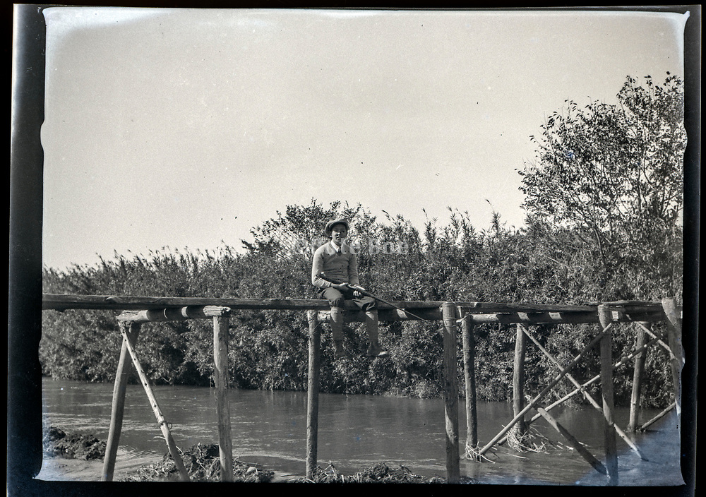 young adult man sitting on a bridge with shotgun Japan ca 1940s