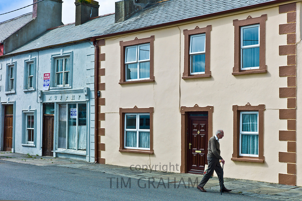 Old man strolls along pavement in, Kilkee, County Clare, West of Ireland