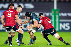 Lloyd Ashley of Ospreys under pressure from Billy Holland of Munster <br /> <br /> Photographer Simon King/Replay Images<br /> <br /> European Rugby Champions Cup Round 1 - Ospreys v Munster - Saturday 16th November 2019 - Liberty Stadium - Swansea<br /> <br /> World Copyright © Replay Images . All rights reserved. info@replayimages.co.uk - http://replayimages.co.uk