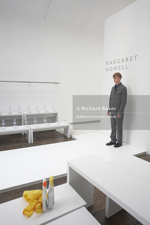 Male model rehearses British couture designer Margaret Howell's Autumn fashion show in her design studio and shop