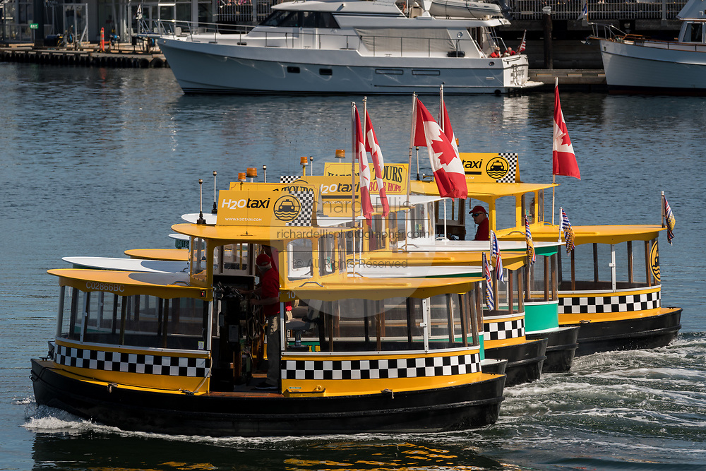 """Tiny harbor taxi ferries perform a synchronized """"Ferry Boat Ballet"""" for crowds at the inner harbor during celebrations marking British Columbia Day August 4, 2018 in Victoria, BC, Canada."""