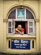 01 AUGUST 2015 - KATHMANDU, NEPAL: A Buddhist monk looks out the window of his monastery near Shree Gha stupa in Kathmandu.      PHOTO BY JACK KURTZ