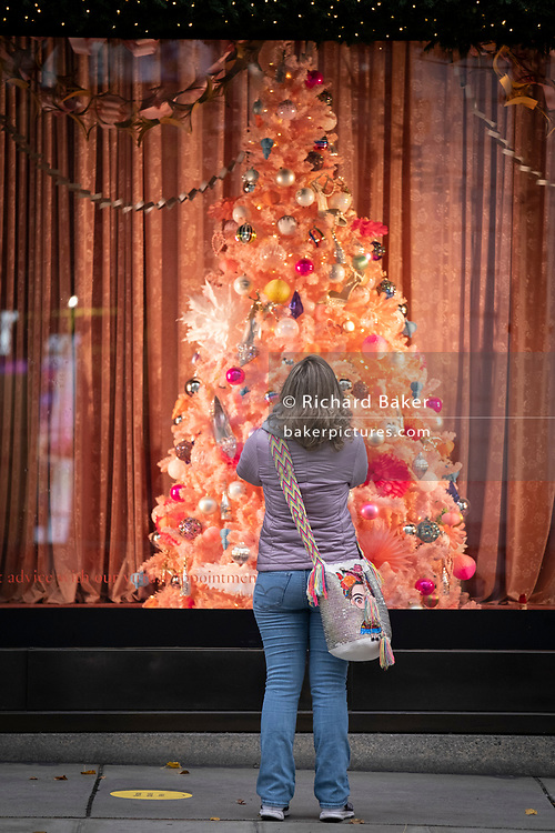 In advance of a re-opening of businesses and before a change to a Tier 2 for London during the second wave of the Coronavirus pandemic, a shopper carrying a Frida Kahlo bag looks at Christmas window displays outside Selfridges on Oxford Street, on 30th November 2020, in London, England. Retailers will once again be open for Christmas business on 3rd December.