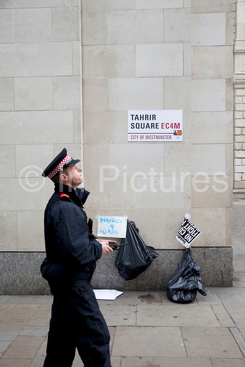 """Policeman walks past the Tahrir Square EC4 City of Westminster road sign. Occupy London protest at St Pauls, October 16th 2011. Protest spreads from the US with this demonstrations in London and other cities worldwide. The 'Occupy' movement is spreading via social media. After four weeks of focus on the Wall Street protest, the campaign against the global banking industry started in the UK this weekend, with the biggest event aiming to """"occupy"""" the London Stock Exchange. The protests have been organised on social media pages that between them have picked up more than 15,000 followers. Campaigners gathered outside  at midday before marching the short distance to Paternoster Square, home of the Stock Exchange and other banks.It is one of a series of events planned around the UK as part of a global day of action, with 800-plus protests promised so far worldwide.Paternoster Square is a private development, giving police more powers to not allow protesters or activists inside."""