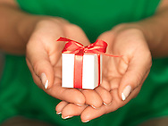 Close up of a woman's hands holding a small white gift box wrapped with a red ribbon.