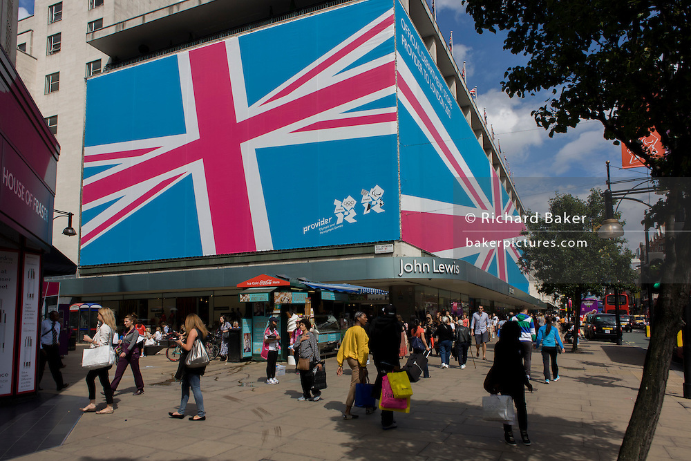 Londoners traffic pass beneath a giant billboard mural wrapped around the exterior of the John Lewis department store in Oxford Street in Central London, during the London 2012 Olympic Games. As part of their partnership with the London Organising Committee of the Olympic Games and Paralympic Games (LOCOG), John Lewis work with their partners giving an opportunity to work at LOCOG and in the build-up to the Games, furnishing lounge and reception areas at Games-time venues.