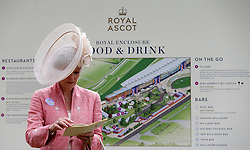 Mrs Rosemary Mehta looks at a programme in front of a map of the Royal Enclosure during day two of Royal Ascot at Ascot Racecourse.
