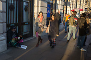 Passers-by ignore a homeless man begging with a sign saying Im hungry, on the pavement in Piccadilly, on 20th January 2020, in London, England.