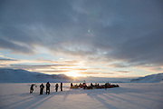 UNIS students wait by their snowmobiles parked on sea ice in Tempelfjorden at the terminus of Tunabreen, Svalbard.