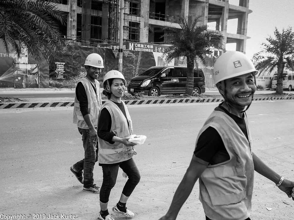 "12 FEBRUARY 2019 - SIHANOUKVILLE, CAMBODIA: Chinese construction workers walk back to a labor camp near the Blue Bay, a Chinese financed resort and casino development, in Sihanoukville. There are about 50 Chinese casinos and resort hotels either open or under construction in Sihanoukville. The casinos are changing the city, once a sleepy port on Southeast Asia's ""backpacker trail"" into a booming city. The change is coming with a cost though. Many Cambodian residents of Sihanoukville  have lost their homes to make way for the casinos and the jobs are going to Chinese workers, brought in to build casinos and work in the casinos.      PHOTO BY JACK KURTZ"