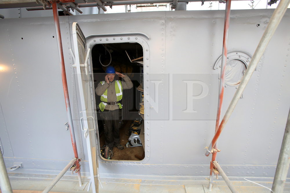 Photo/Paul McErlane© Licensed to London News Pictures. 28/04/2016. Belfast County Antrim, Northern Ireland, UK. HMS Caroline's restoration is the biggest World War One project of the century. Funded by Heritage Lottery Fund and supported by DETI, the Portsmouth-based National Museum of the Royal Navy undertook the restoration project three years ago. It will be completed in time for the centenary of the Battle of Jutland on May 31 2016. A workman gives a salute. Photo credit : Paul McErlane/LNP